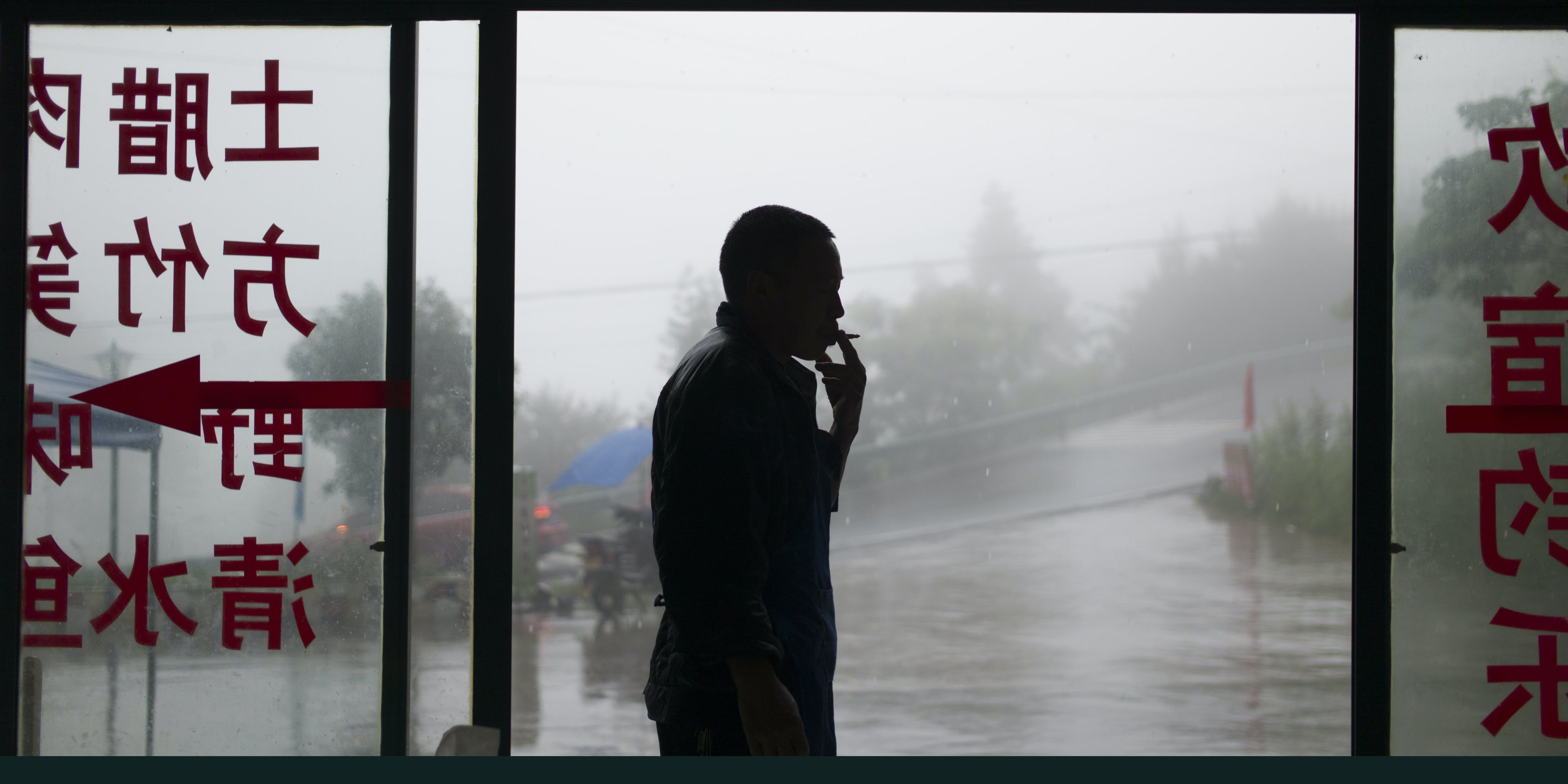 A man smokes on the outskirts of Chongqing, southwest China, on June 1, 2017. (Photo by Fred Dufour/AFP via Getty Images)