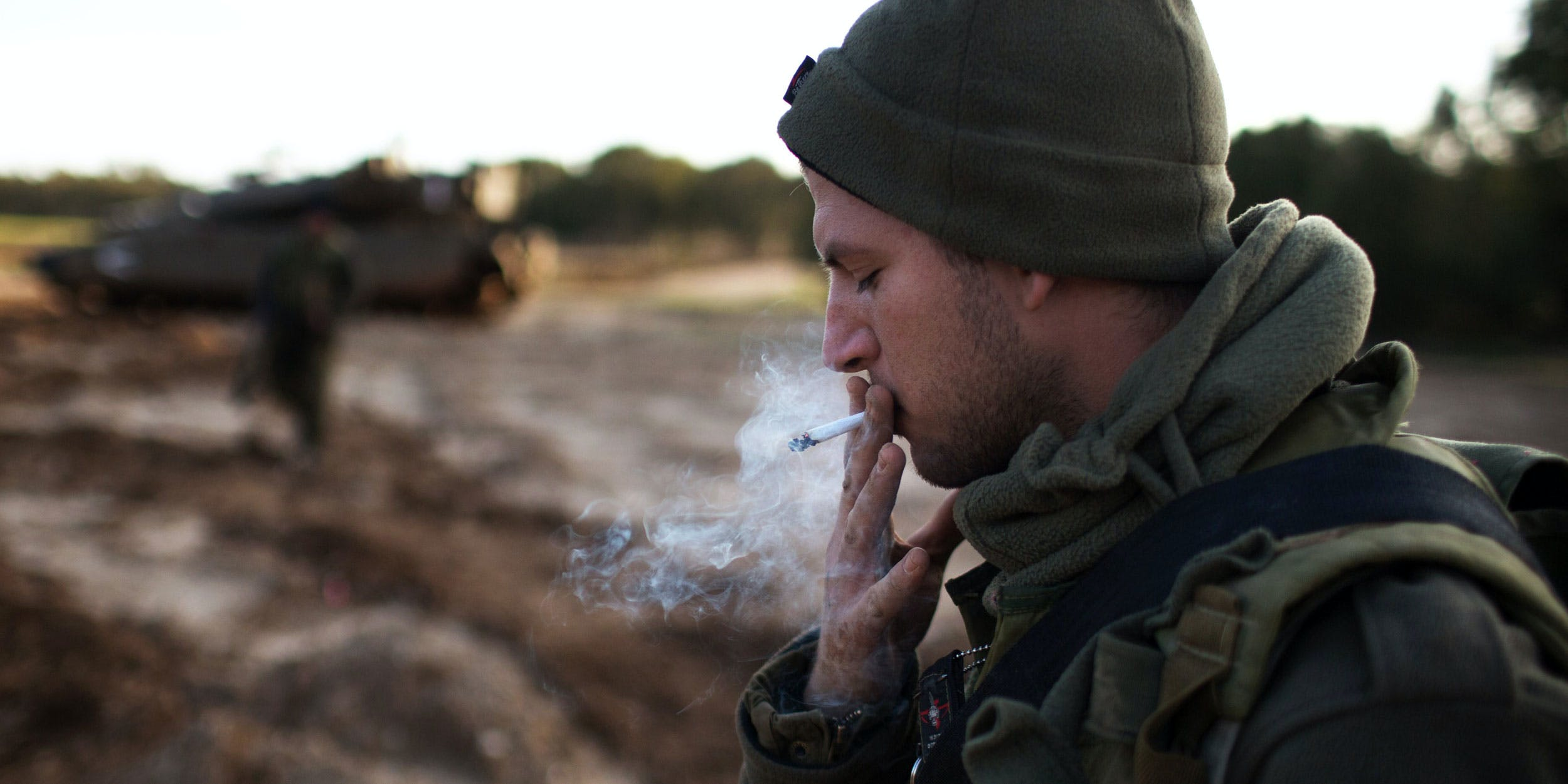An Israeli soldier smokes a cigarette next to his Merkava tank positioned along the southern border with the Gaza Strip on December 25, 2013. Many Israelis smoke cannabis to cope with the trauma of growing up in a war torn country. (Photo by Mehahem Kahana/AFP/Getty Images)
