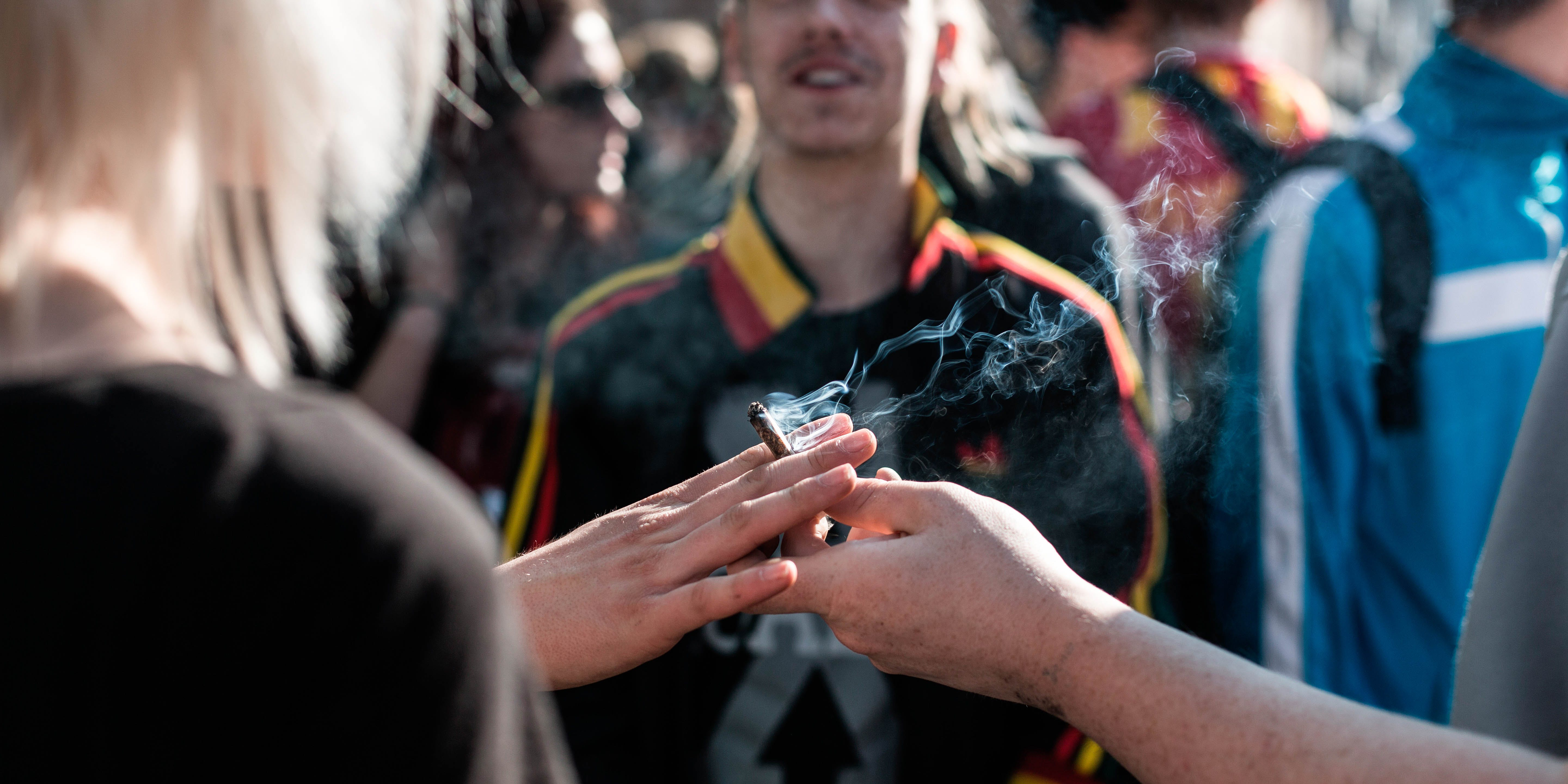 A joint is passed from one hand to another at the annual Pro 420 Cannabis Day in Copenhagen. Denmark 20/04 2014. A recent study found neighborhood dispensaries don't increase adolescent cannabis use