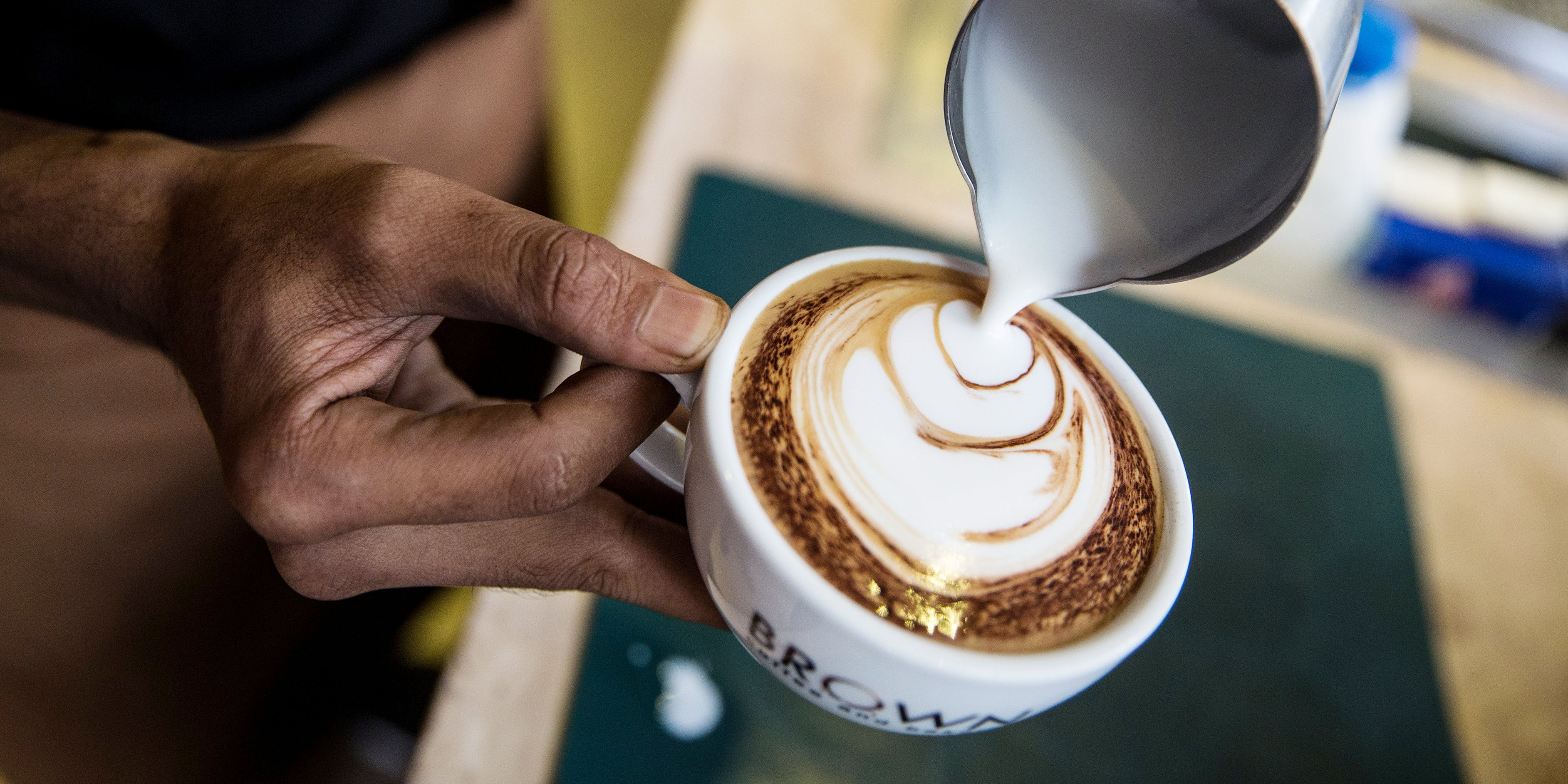 An employee makes coffee foam art inside a Brown Coffee Co. cafe at the T.K. Avenue shopping area in Phnom Penh, Cambodia, on Thursday, July 26, 2018. In this story, we report on how Canadian Coffee Chain Second Cup intends to convert some of its cafes into dispensaries.