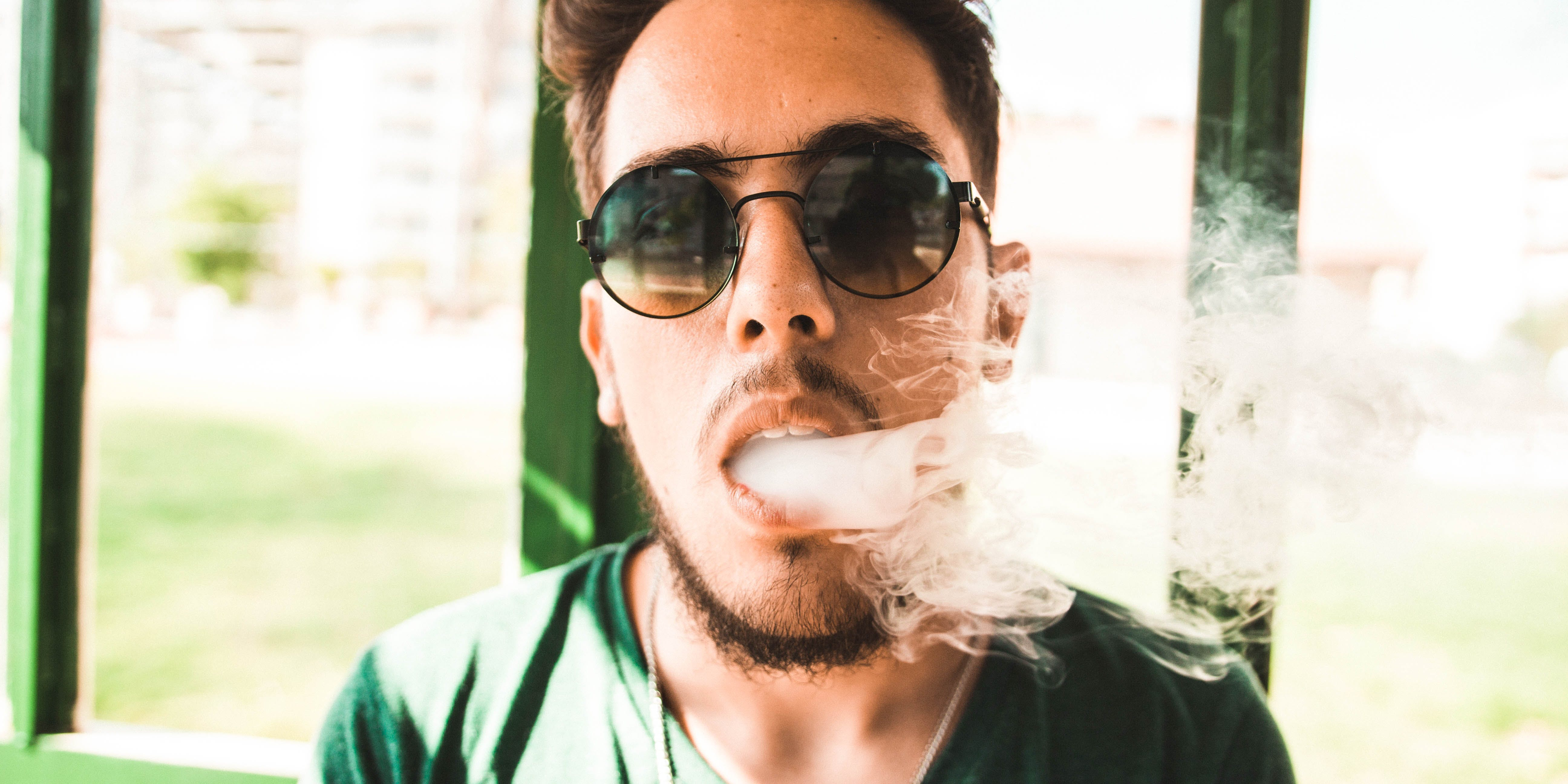 "A man is shown exhaling smoke. In this article, we ask ""Does CBD Vape Oil Get You High?"""