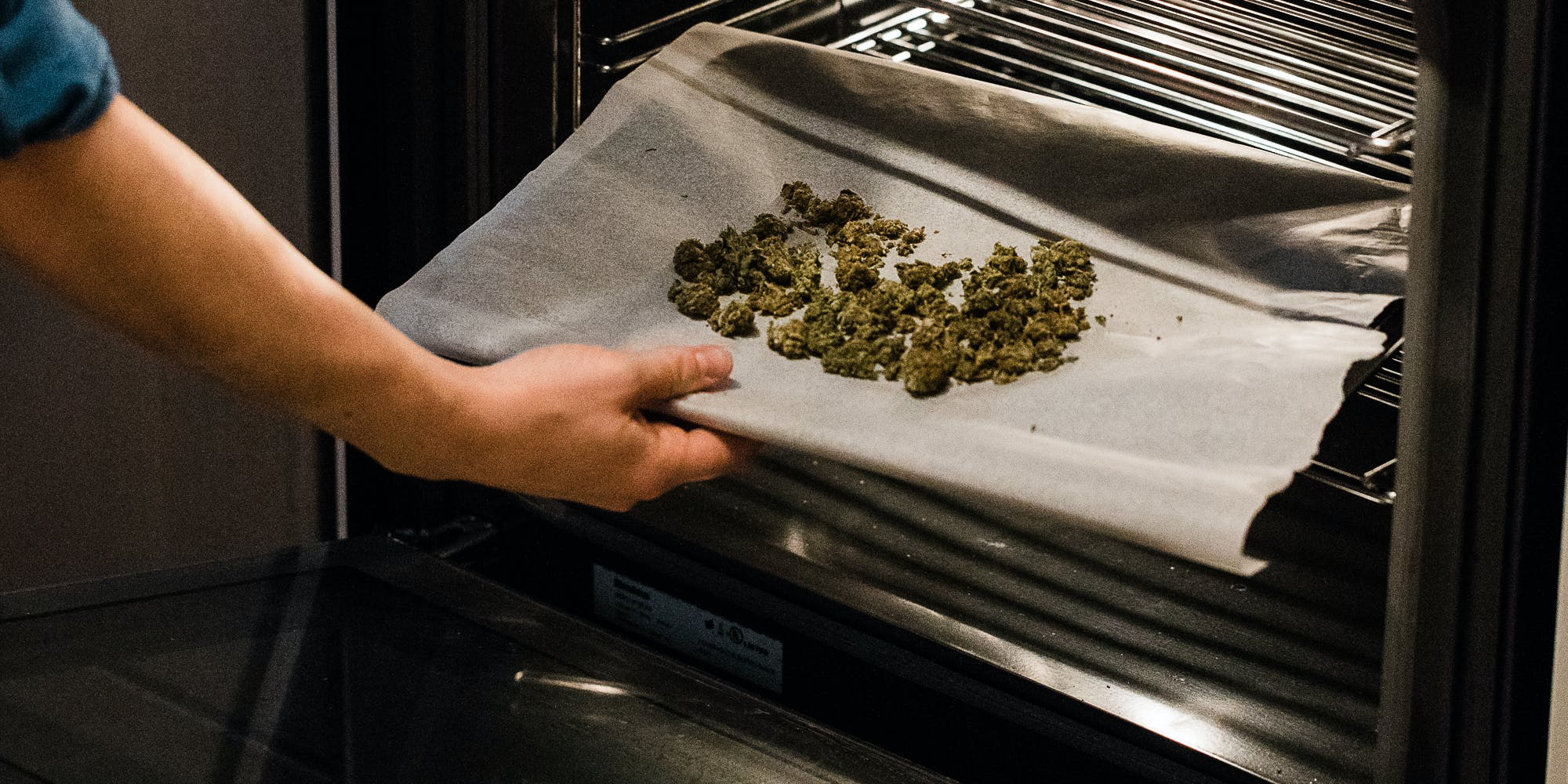 Cannabis flower on a cooking sheet being inserted into an oven. In this article, Herb explores if cooking with cannabis gets rid of the THC.