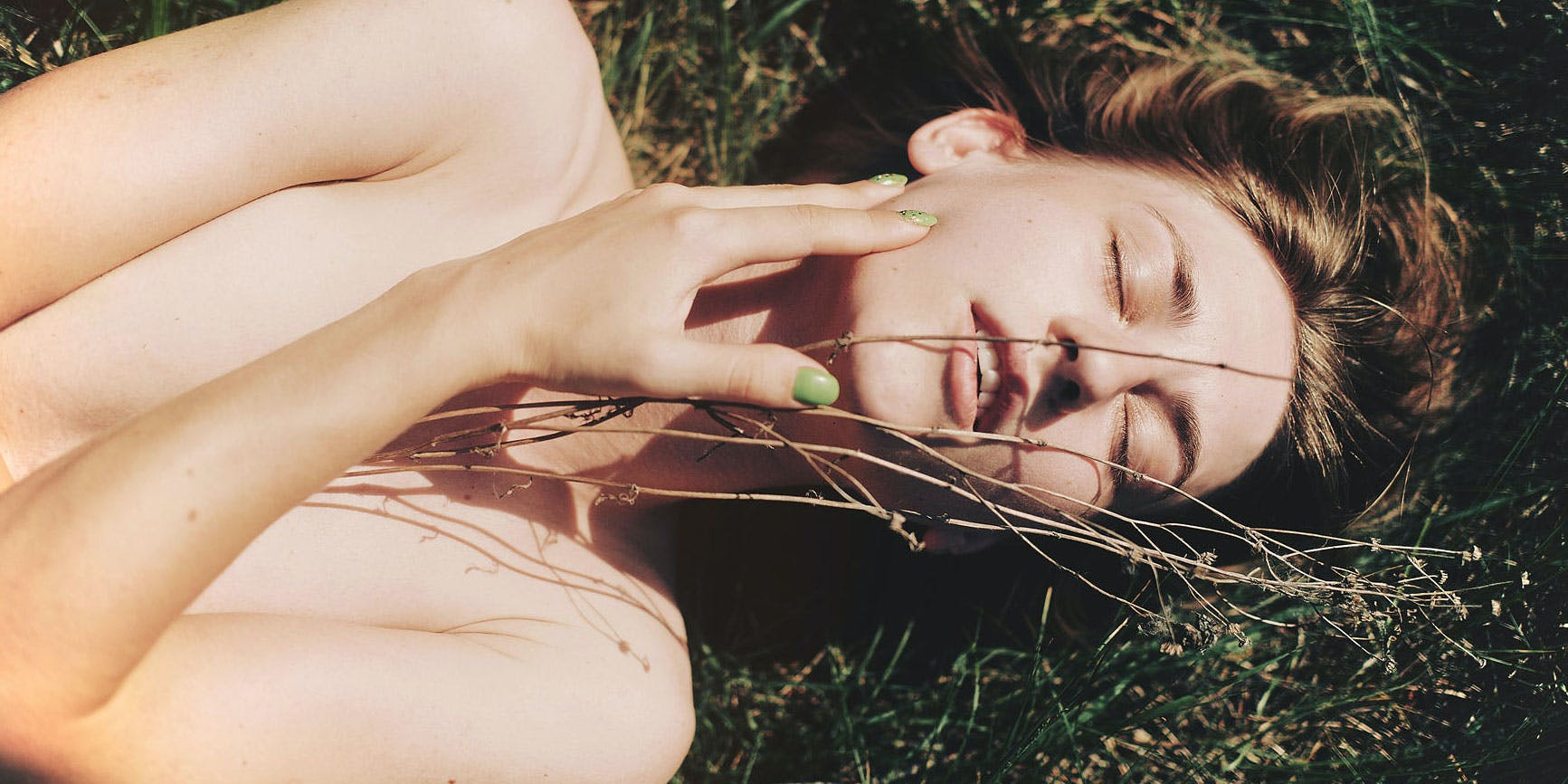 woman lying down in a field. In this article, Herb explores people can use CBD for endometriosis.