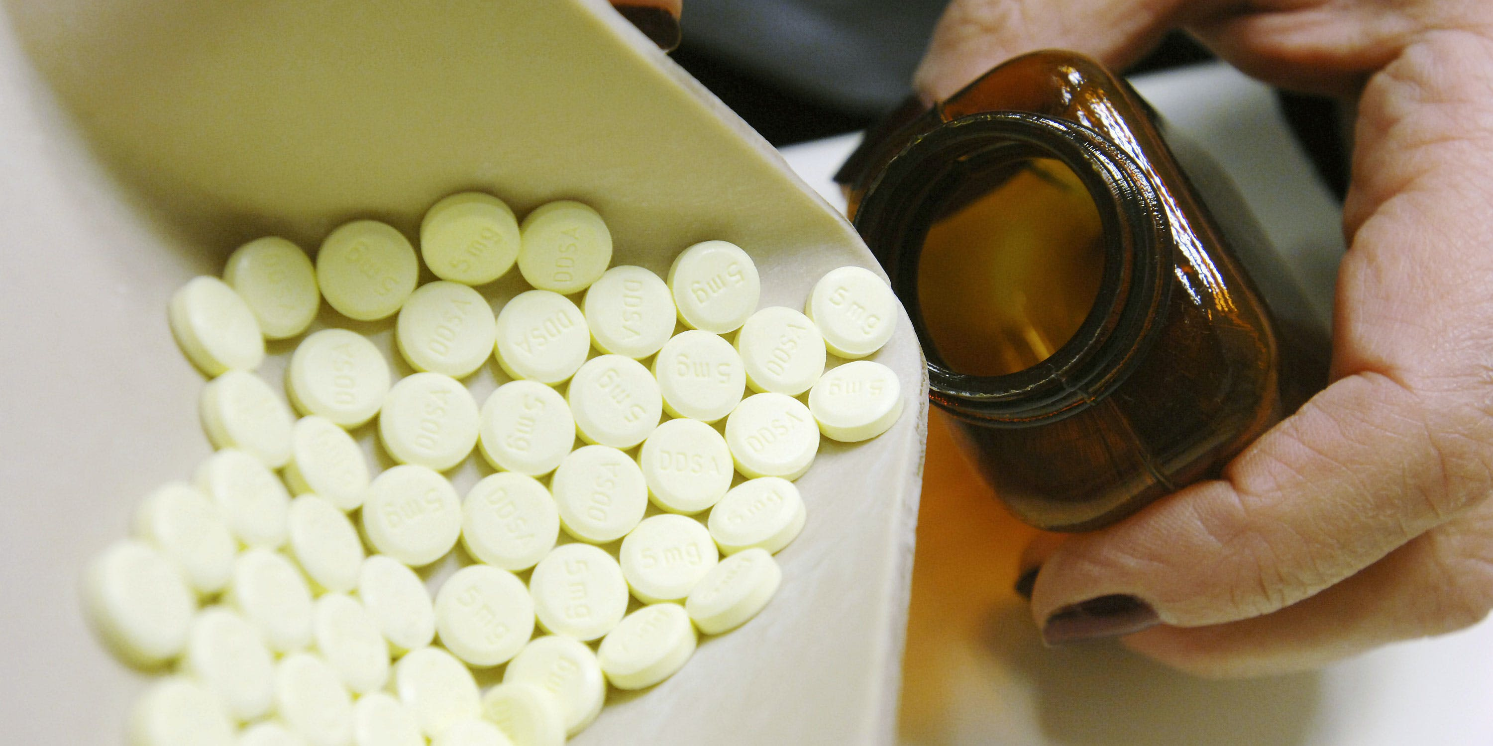 Close-up of a pharmacist dispensing tablets from a pill bottle. Research is beginning to emerge about the use and benefits of cannabis as a sleep aid.