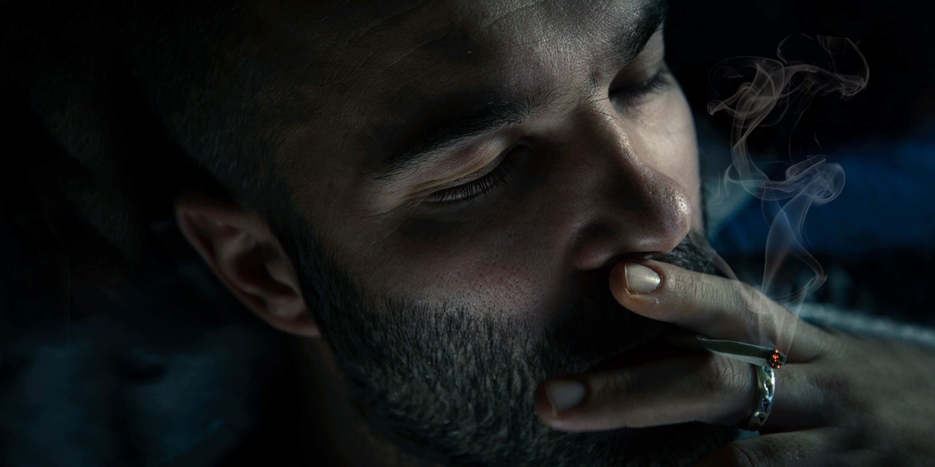 Close-up photo of mid-adult man smoking cigarette in the dark. He appears deep in thought, likely pondering one of life's many philosophical questions.