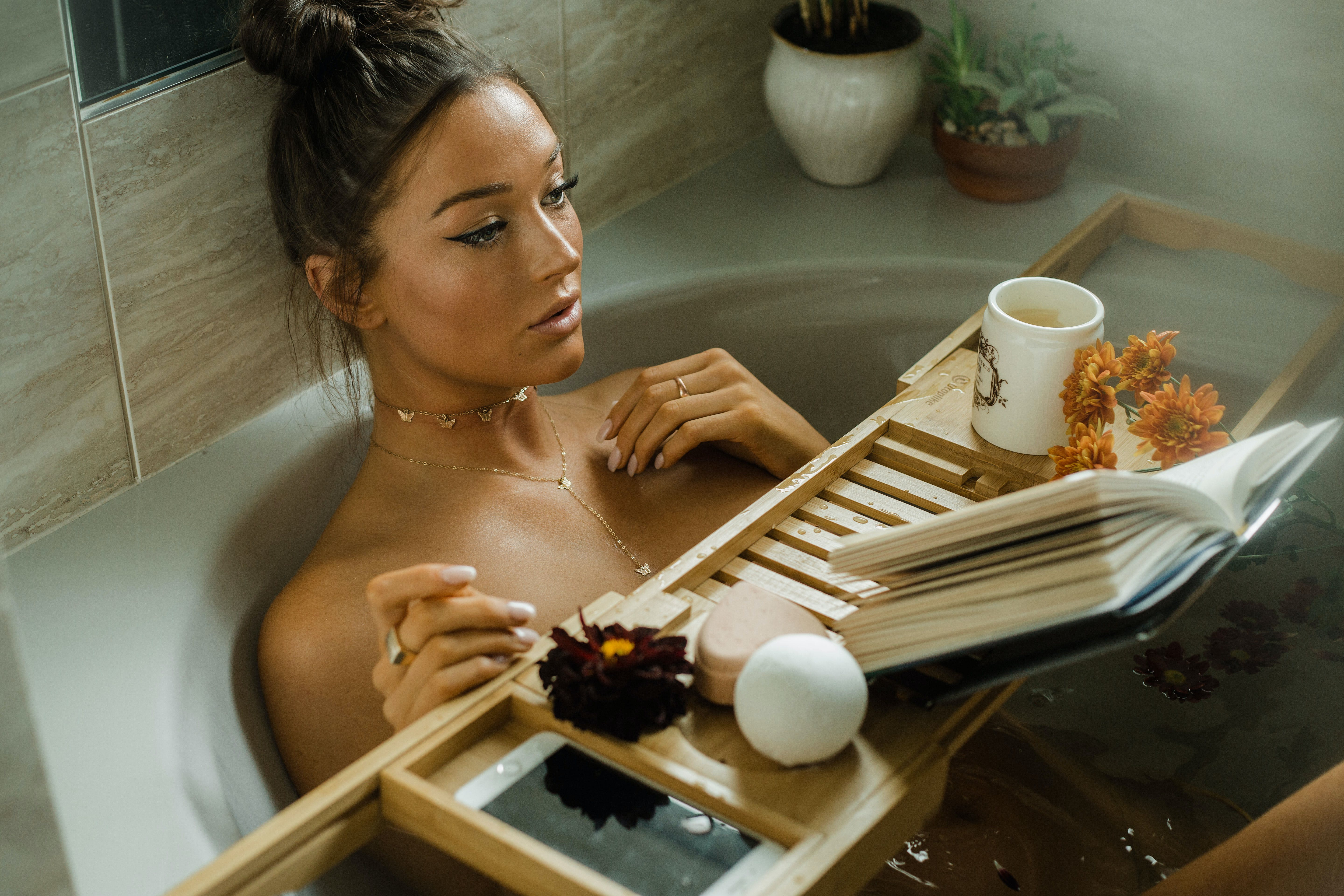 A woman relaxes in the tub with the best CBD bath bombs
