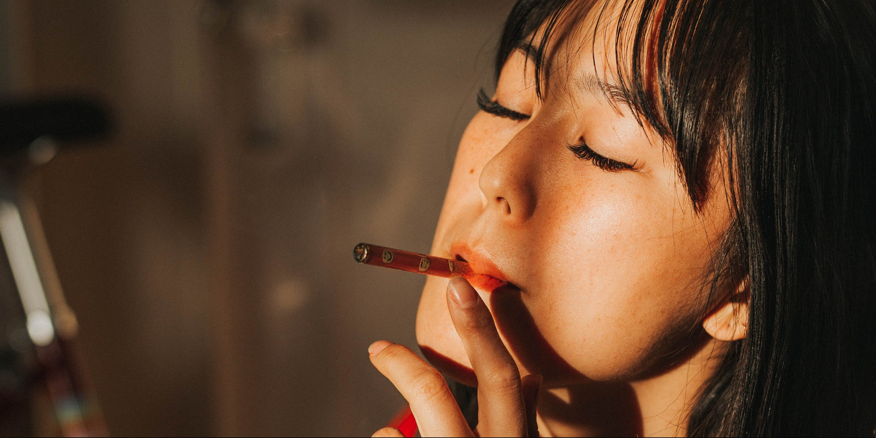 A woman smokes with her eyes closed. A woman smokes while sitting down. A new study cites that problematic behavior was not shown to increase in tandem with legalized cannabis laws.