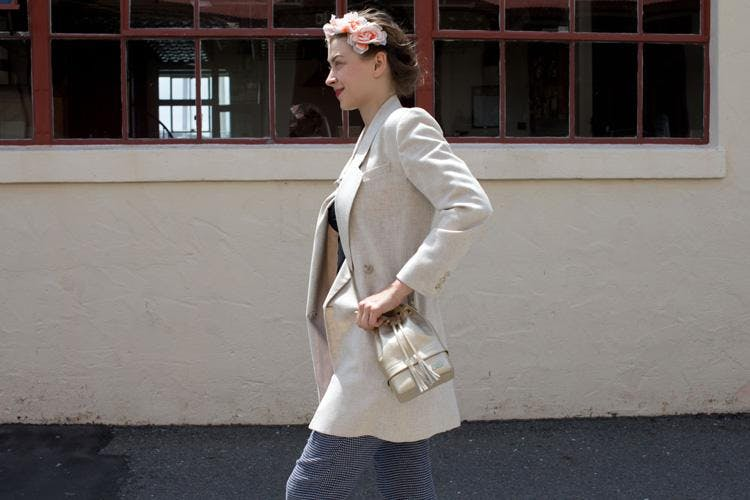 A woman with a floral headband and a cream blazer wears a stash bag that looks just like a designer handbag