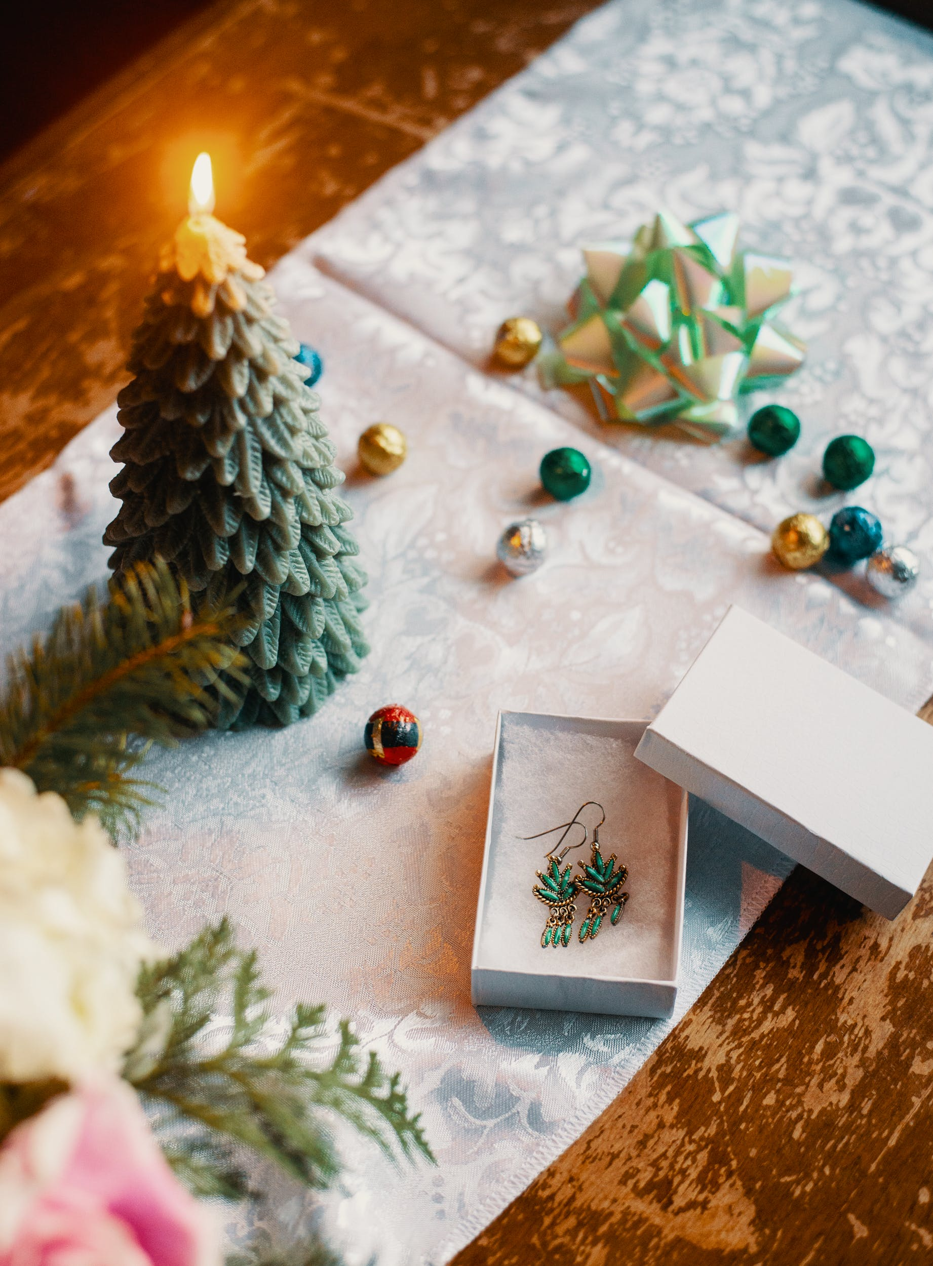 A decorative spread with a Christmas tree candle, several baubles and a green bow. There is a box with two weed leaf shaped earrings
