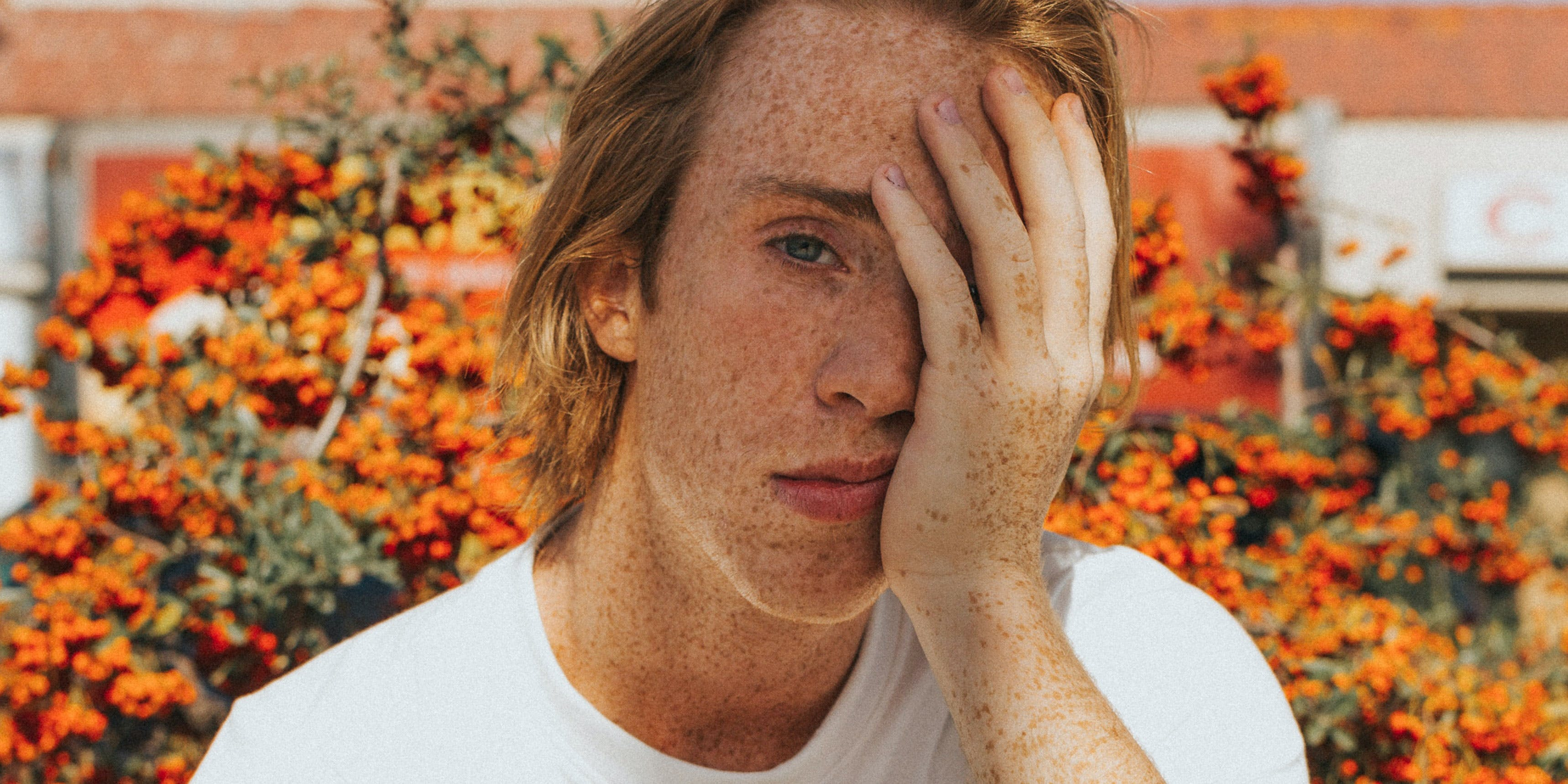 Here, a man with a migraine is shown holding his head. In this article, we explore the best strains for migraines