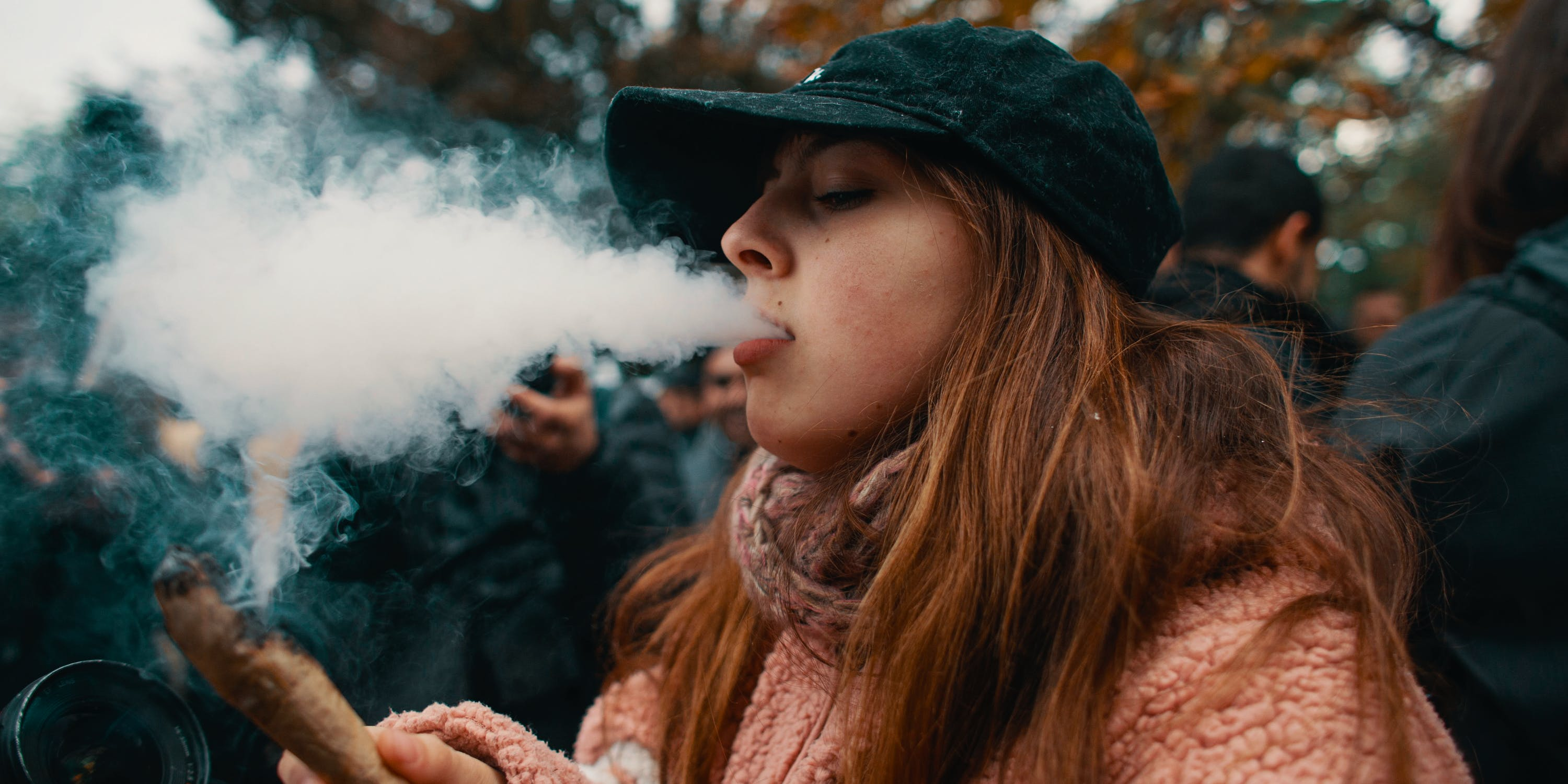A woman consumes cannabis, to find out how the recent midterms affected legal cannabis, read more here.