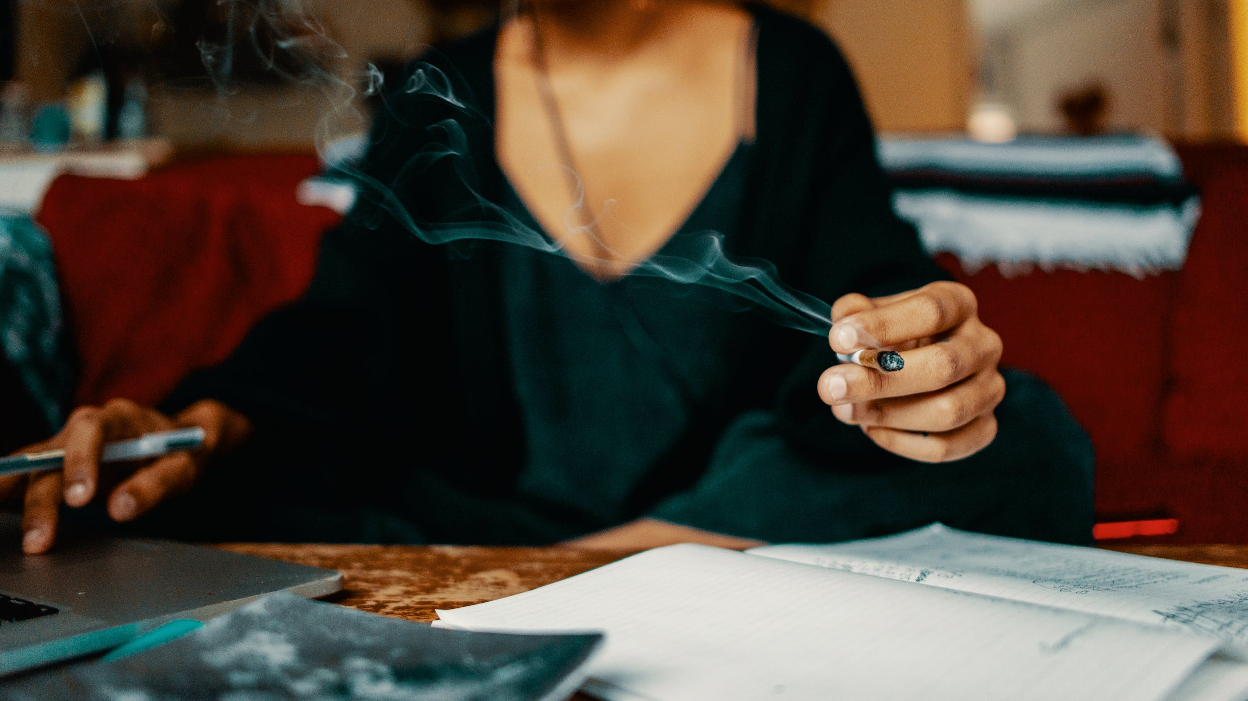 A woman smokes a joint filled with one of the best CBD strains