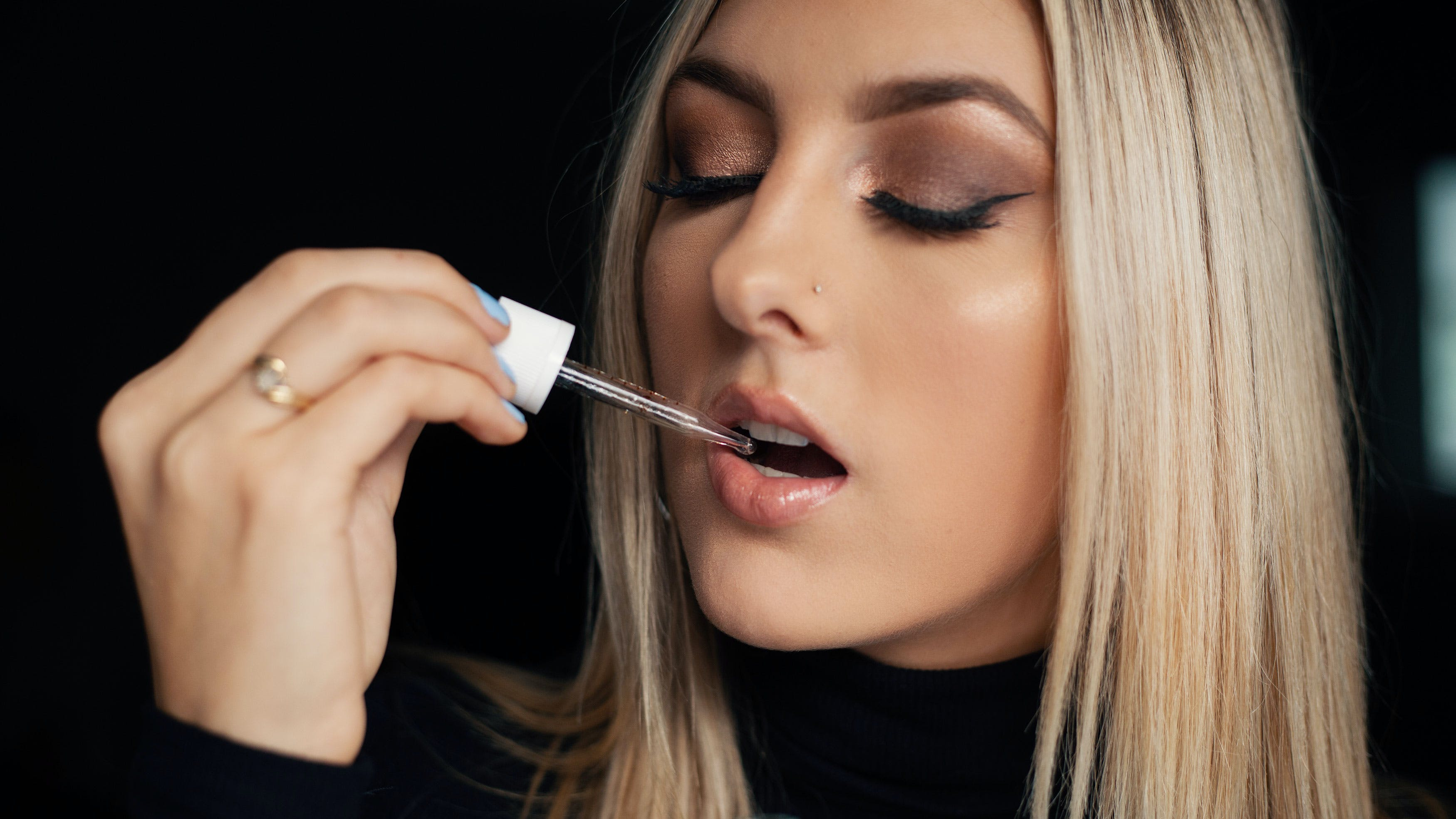 A woman takes a dropper of liquid CBD after learning about CBD drug interactions