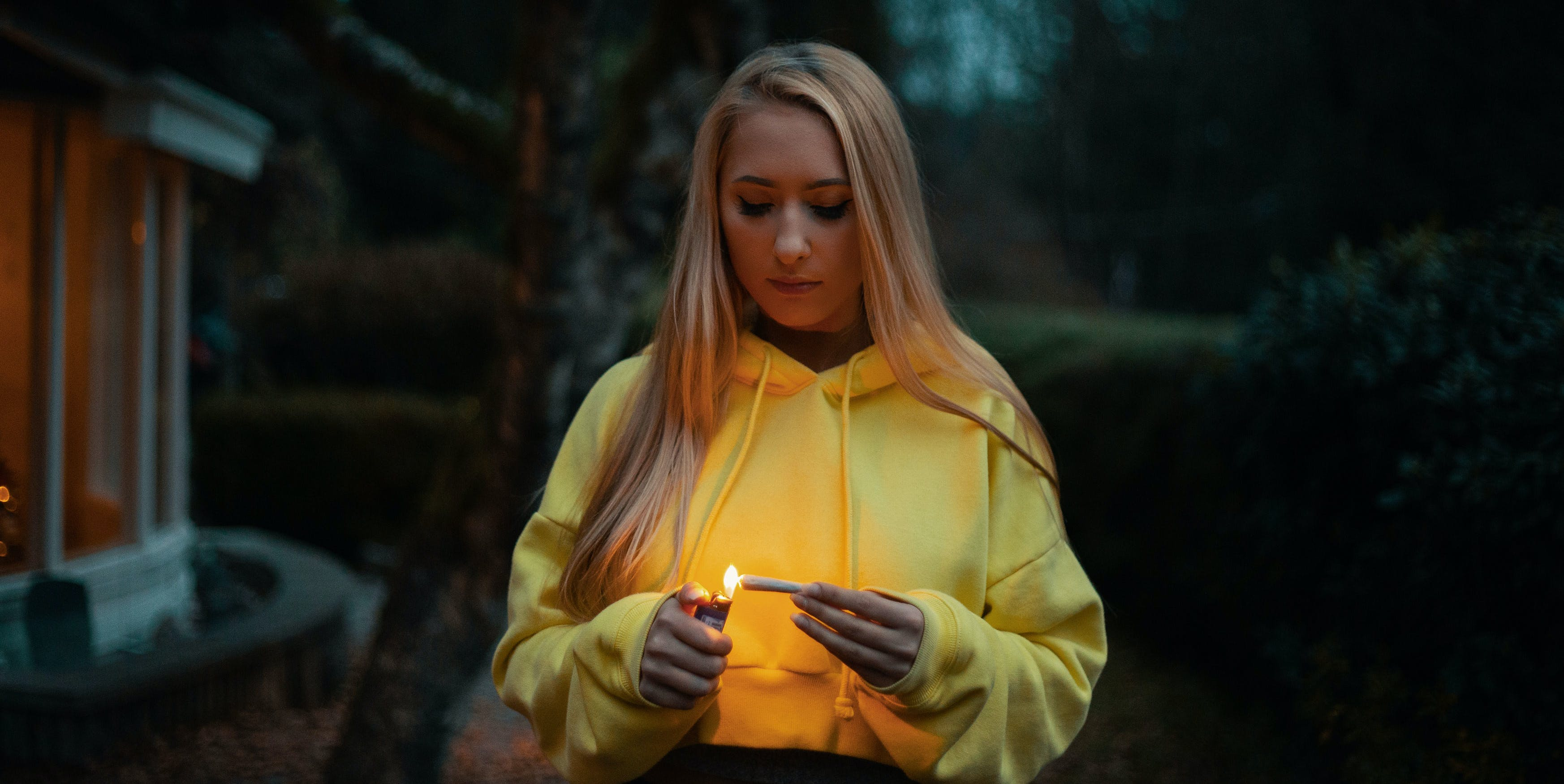 A woman in a yellow hooded sweatshirt smoking weed before bed