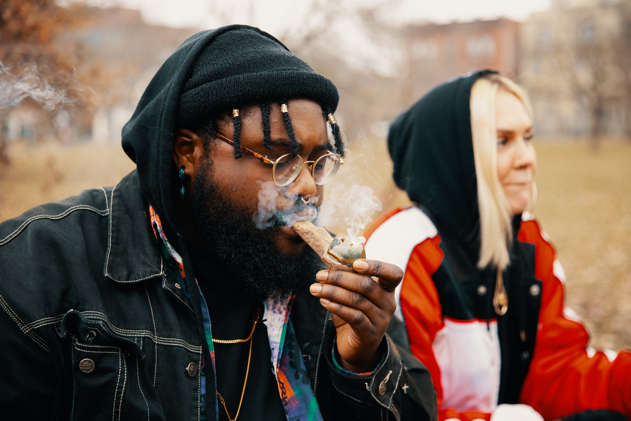 A man and a woman use a pipe after learning how to smoke bubble hash
