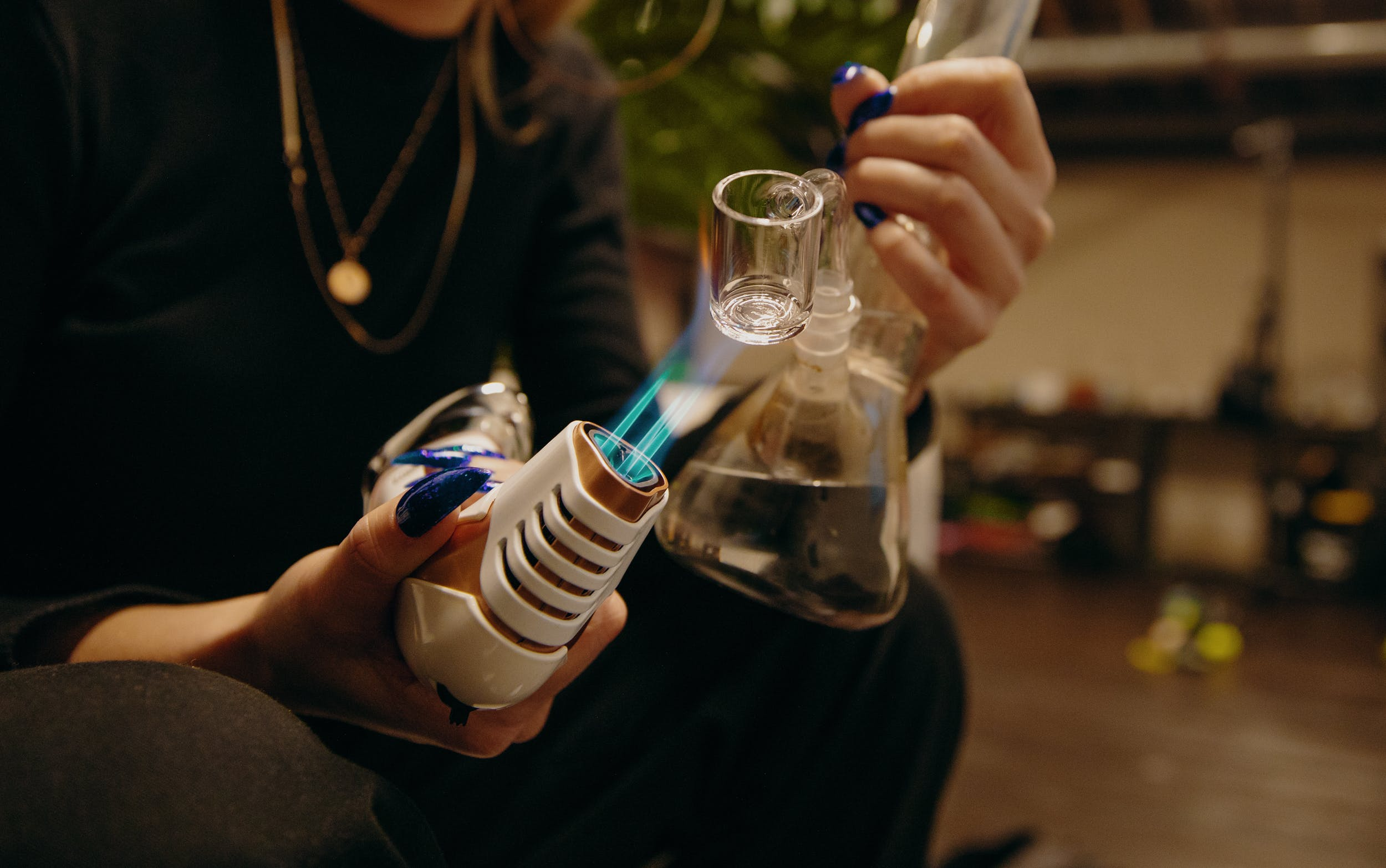 How to Smoke Hash Oil: A woman uses a butane torch to heat up a dab rig