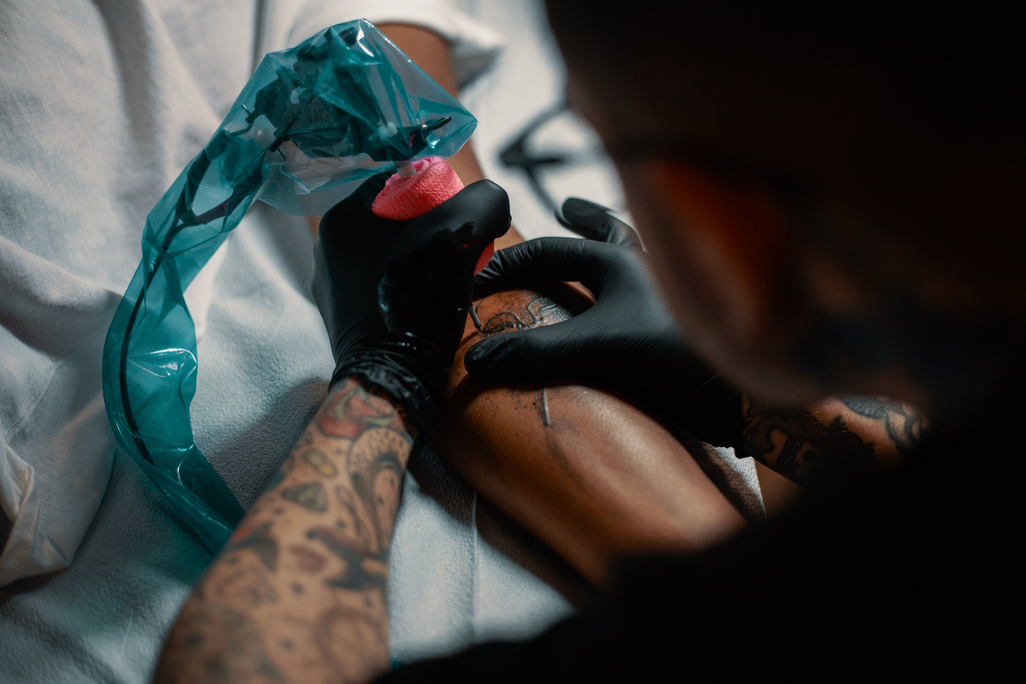 Smoking Weed Before a Tattoo: A tattoo artist with gloved hands operating a machine on a mans arm.
