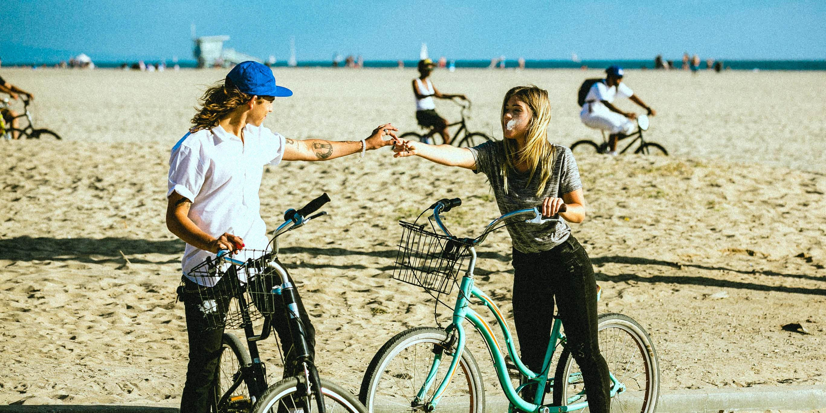 A couple share a joint on the beach. There are now more weed dating apps on the market to help people with a mutual love for the herb find their counterpart.