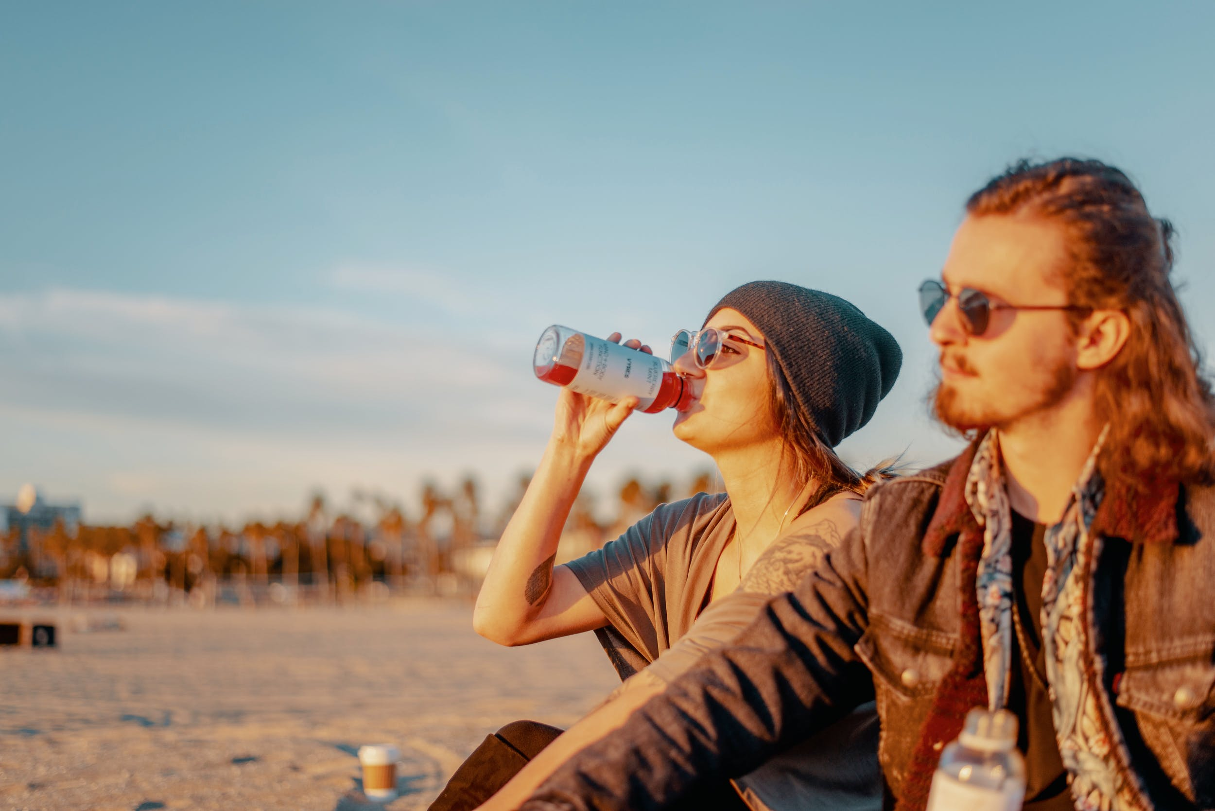 Two people sit on a beach enjoying some of the best CBD drinks