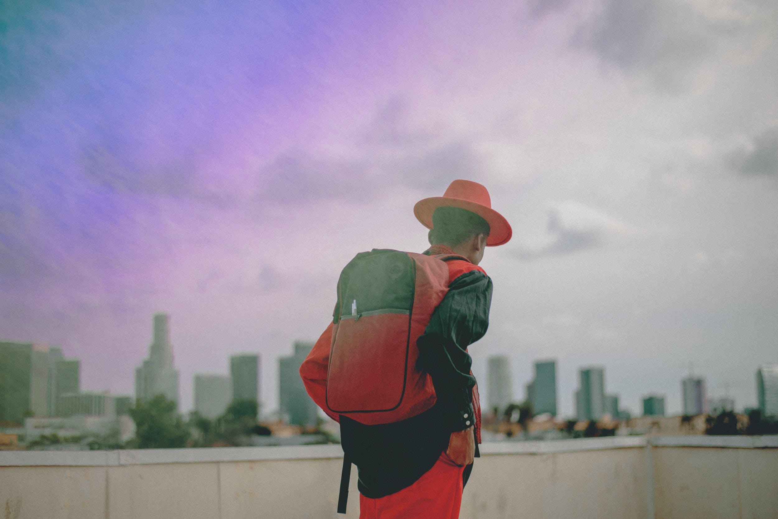 Standing before a skyline with a purple sunset, a man in a red hat with one of the best stash bags, the Skunk Bag, over his shoulder.