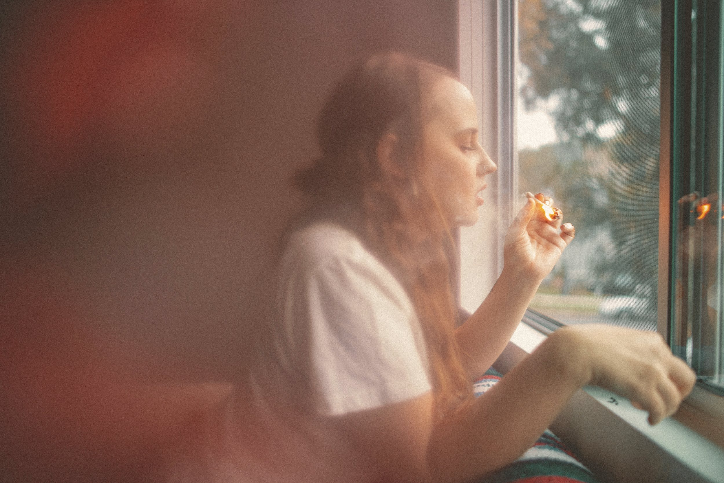 A woman leans out of a window smoking one of the best weed strains