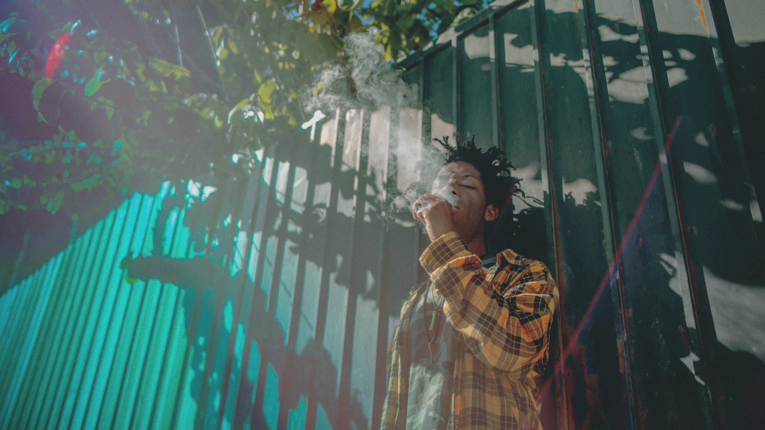 A man leans against a fence and enjoys one of the best weed vaporizers