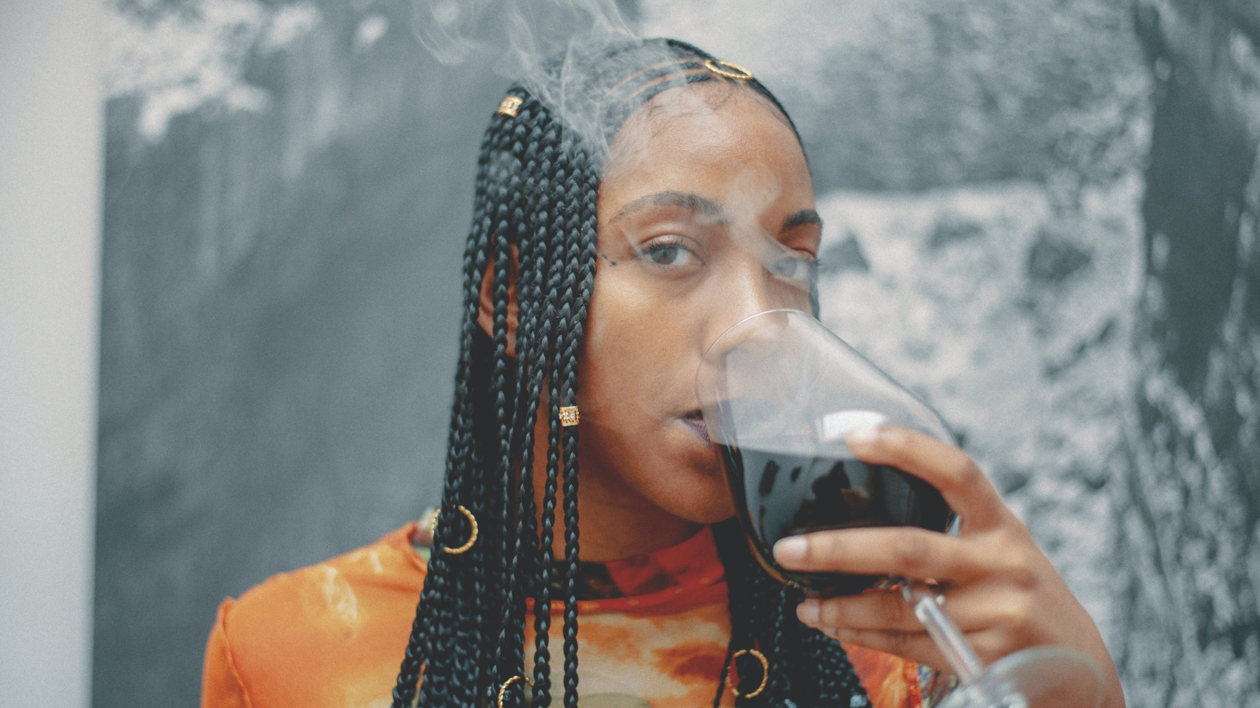A woman takes a sip of weed wine in a cloud of smoke