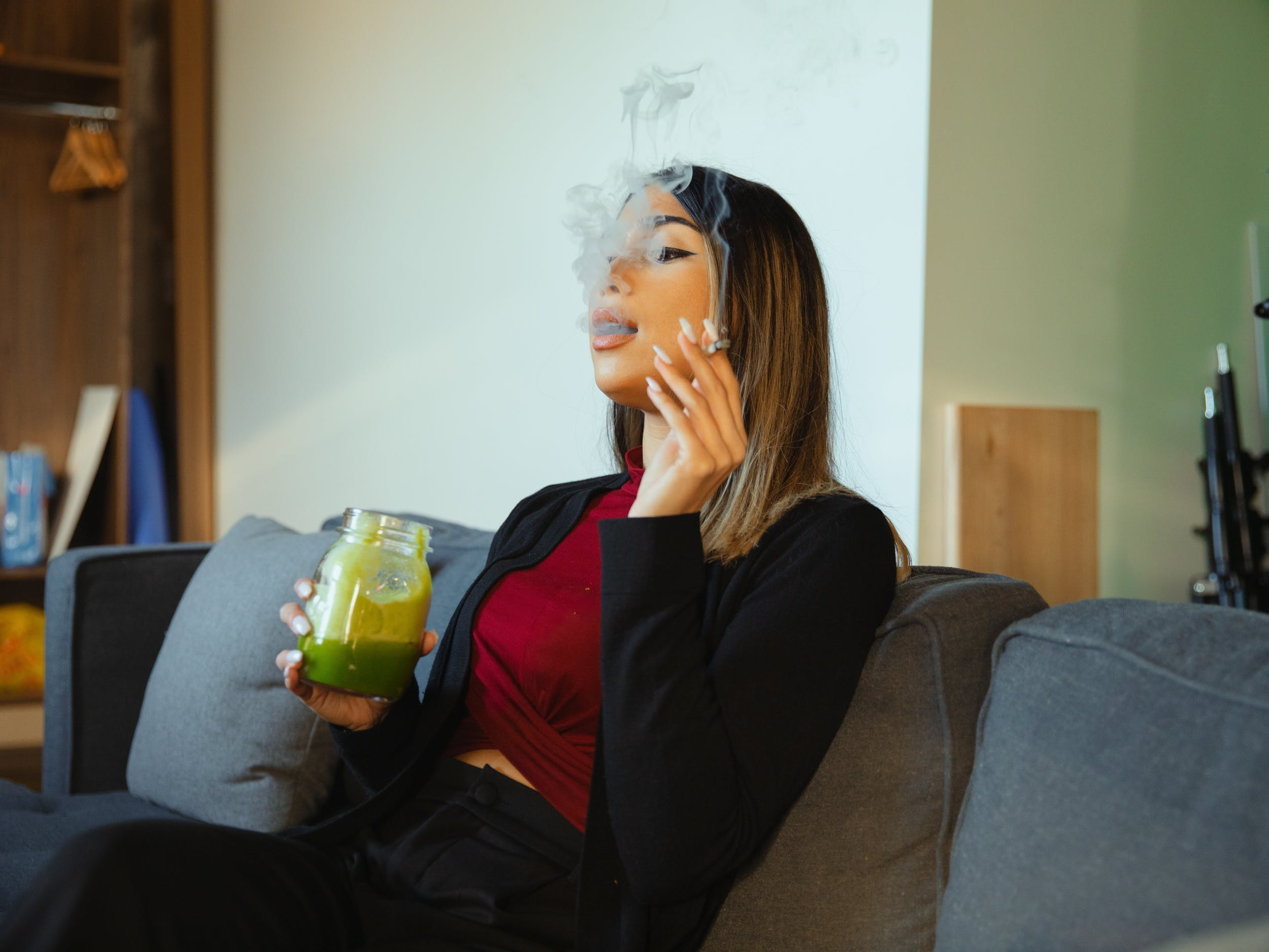 A woman sits on a couch smoking a joint and drinking a mason jar full of Bhang. Learn how to make bhang at home with this guide.