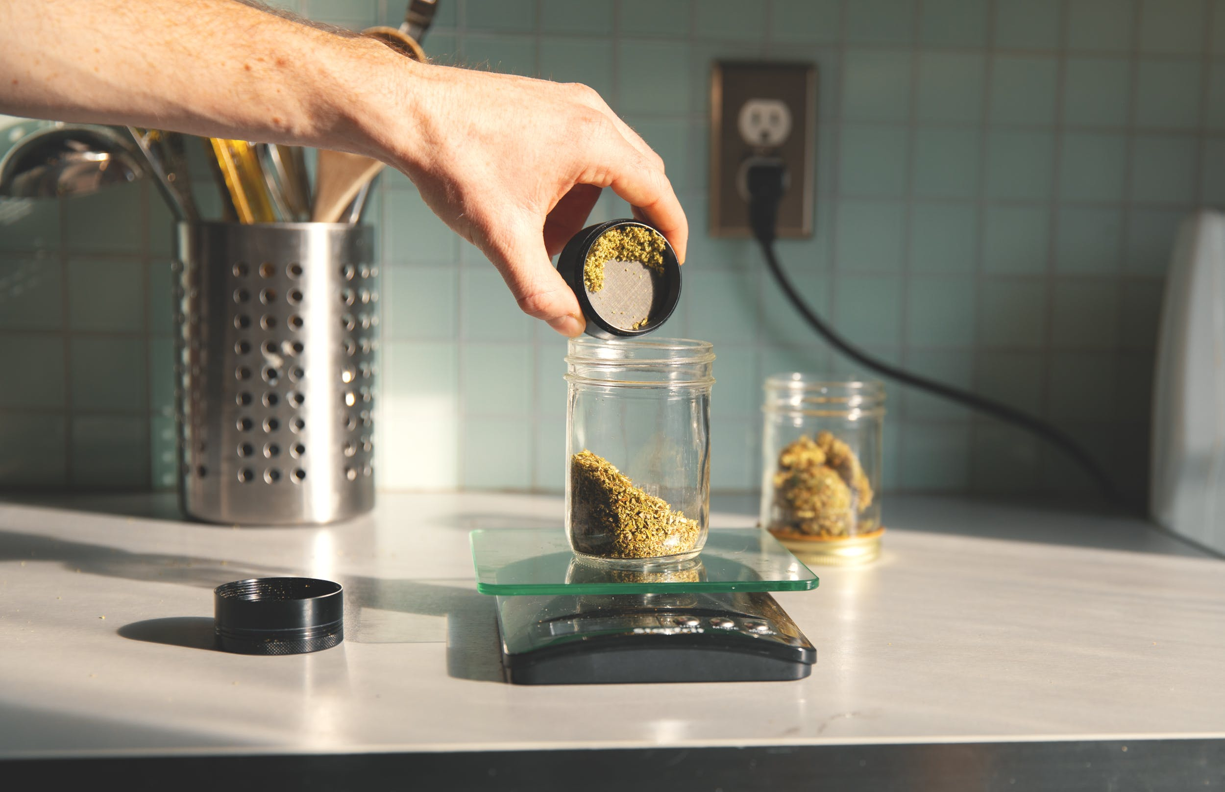 A hand pours ground flower into a jar as part of our how to make THC pills guide