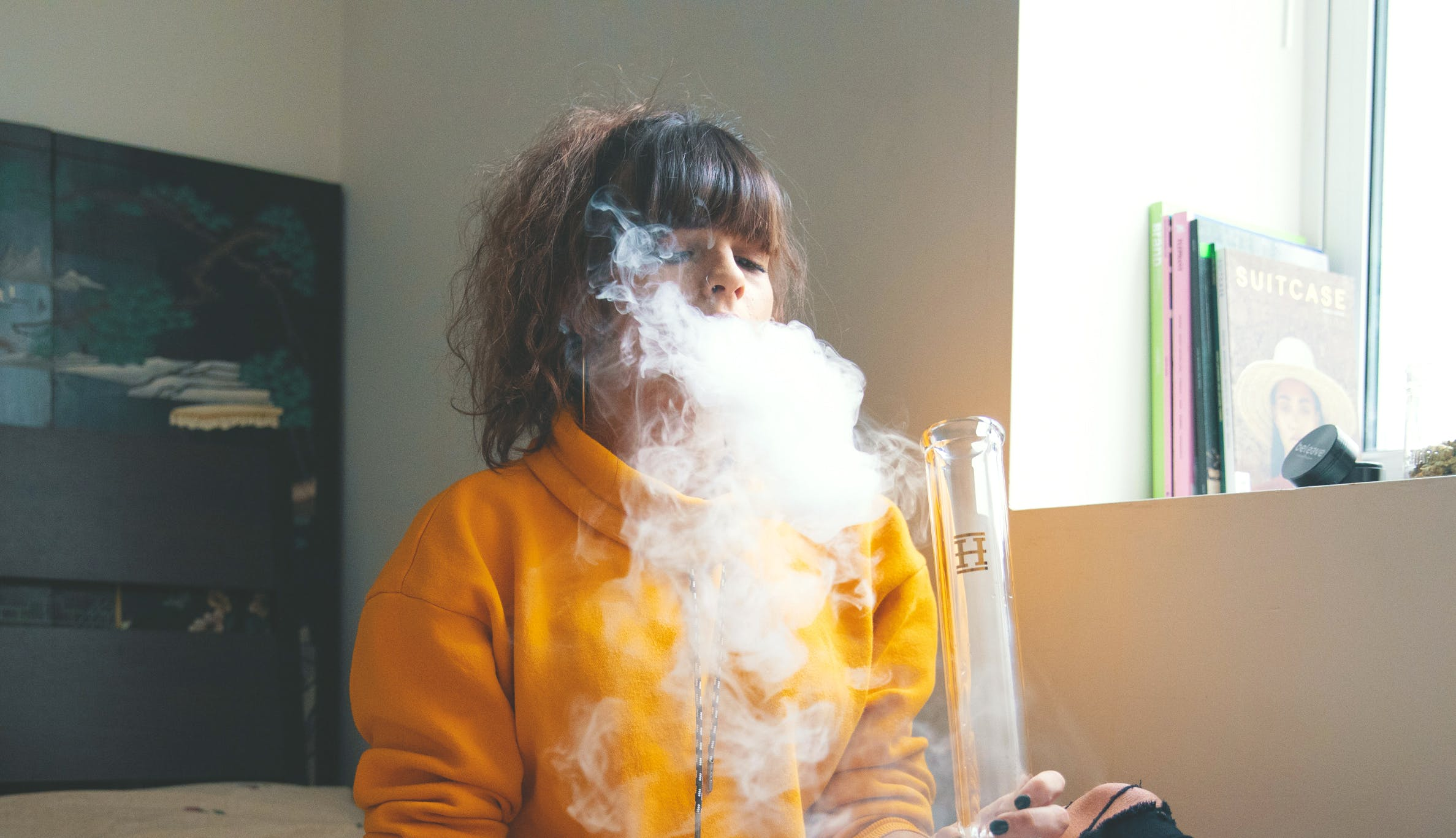 How to Make a Dab Station: A woman exhales a puff of smoke