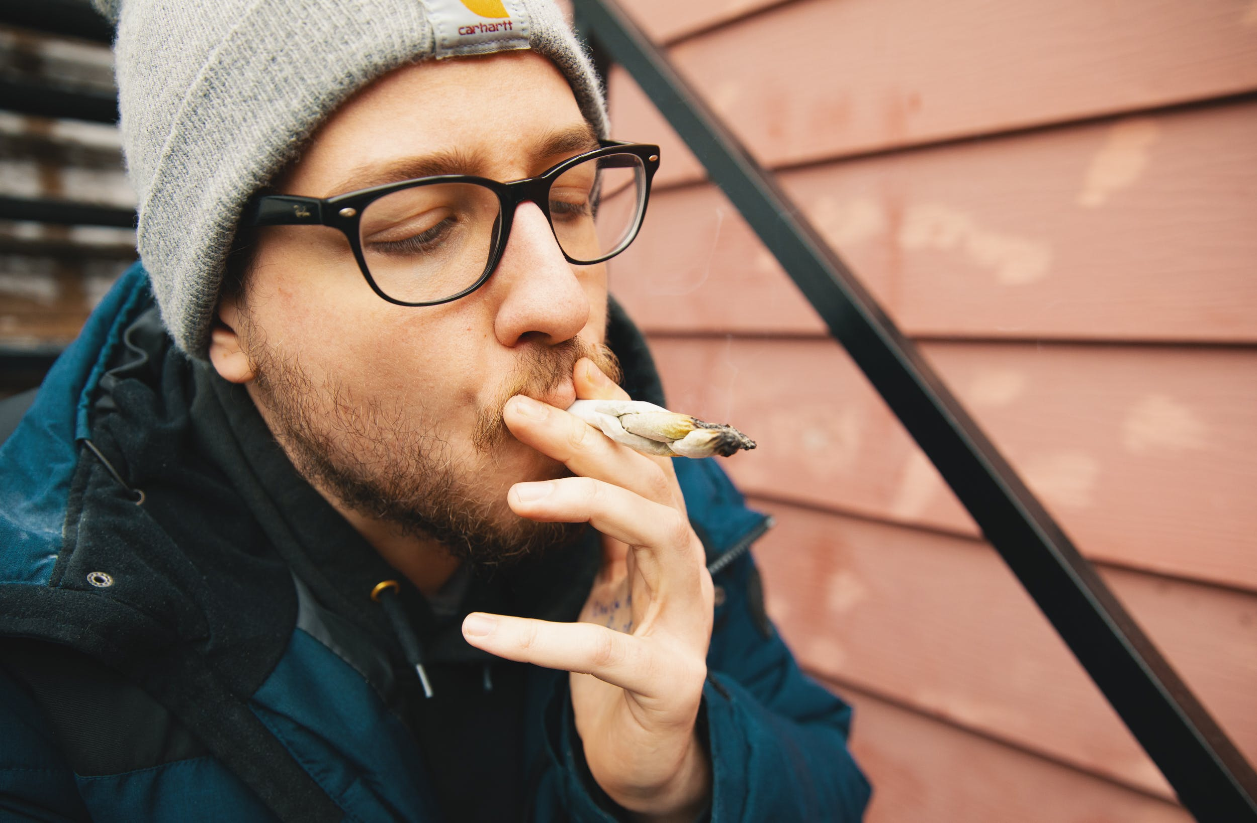 After learning how to roll a braided joint, a man smokes weed on some steps.