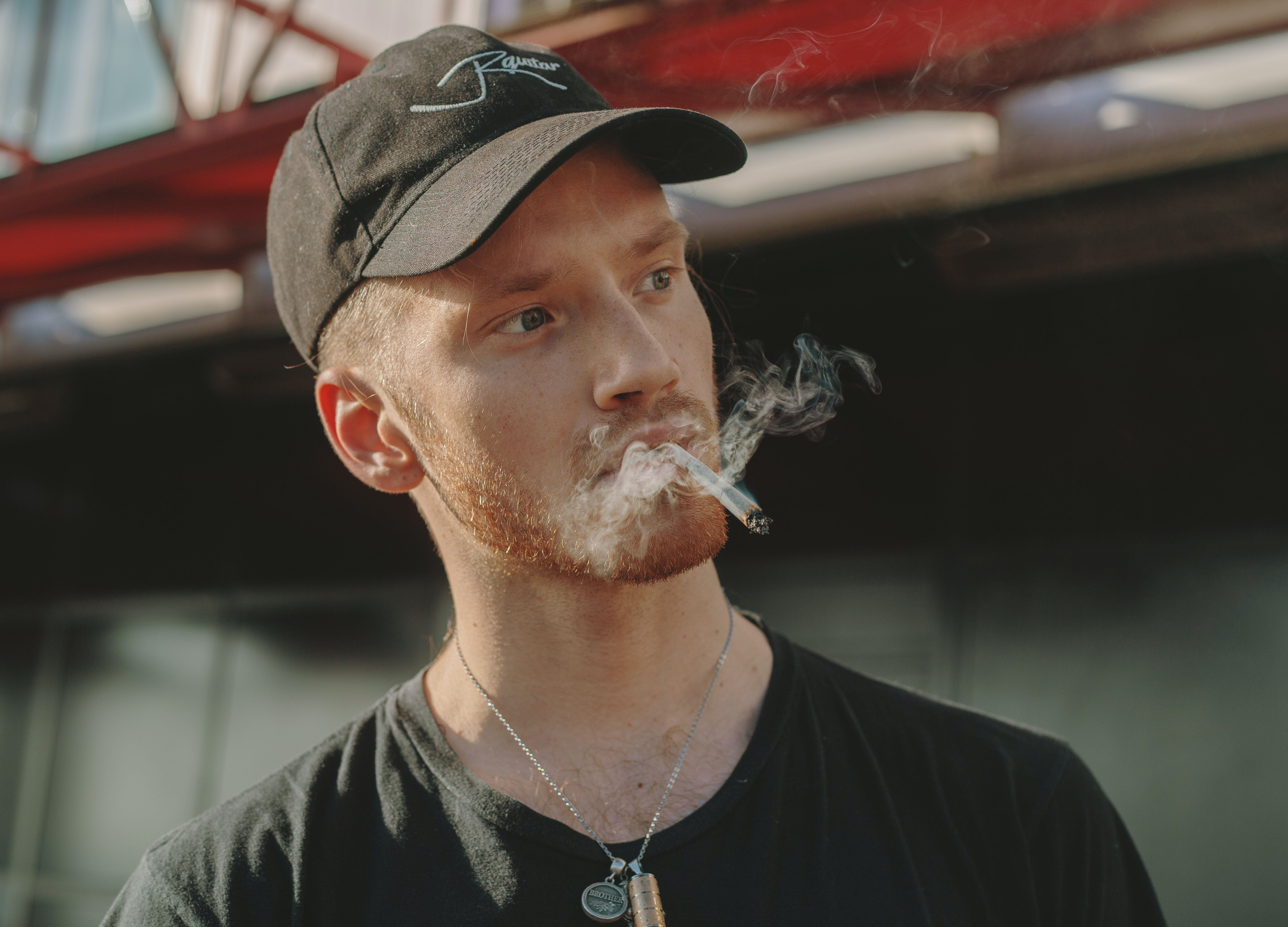 Is smoking weed bad for your lung? A man exhales smoke, while wearing a hat