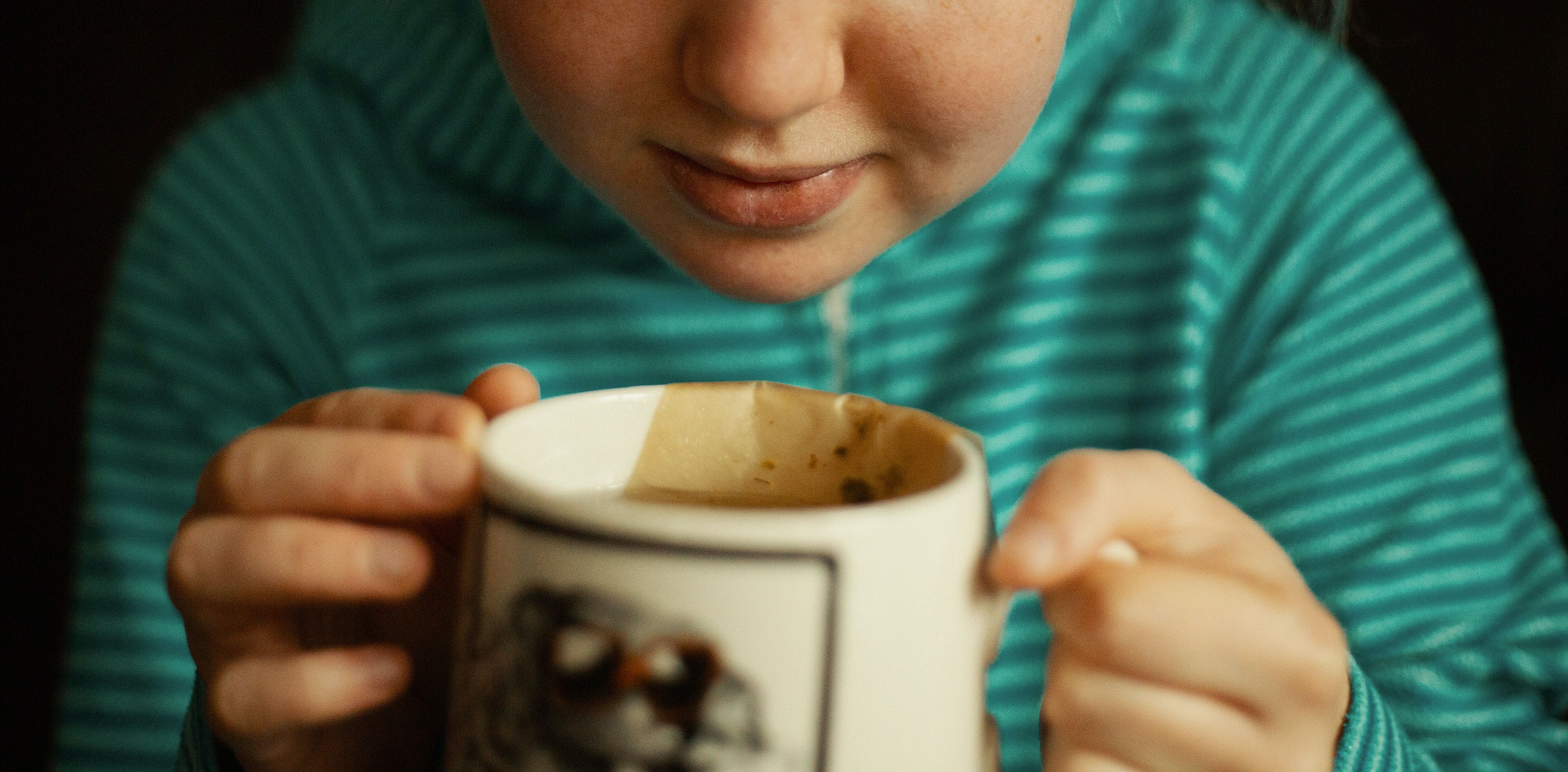 Someone drinks from a tea cup, which can be a good way to avoid smoking weed and being sick