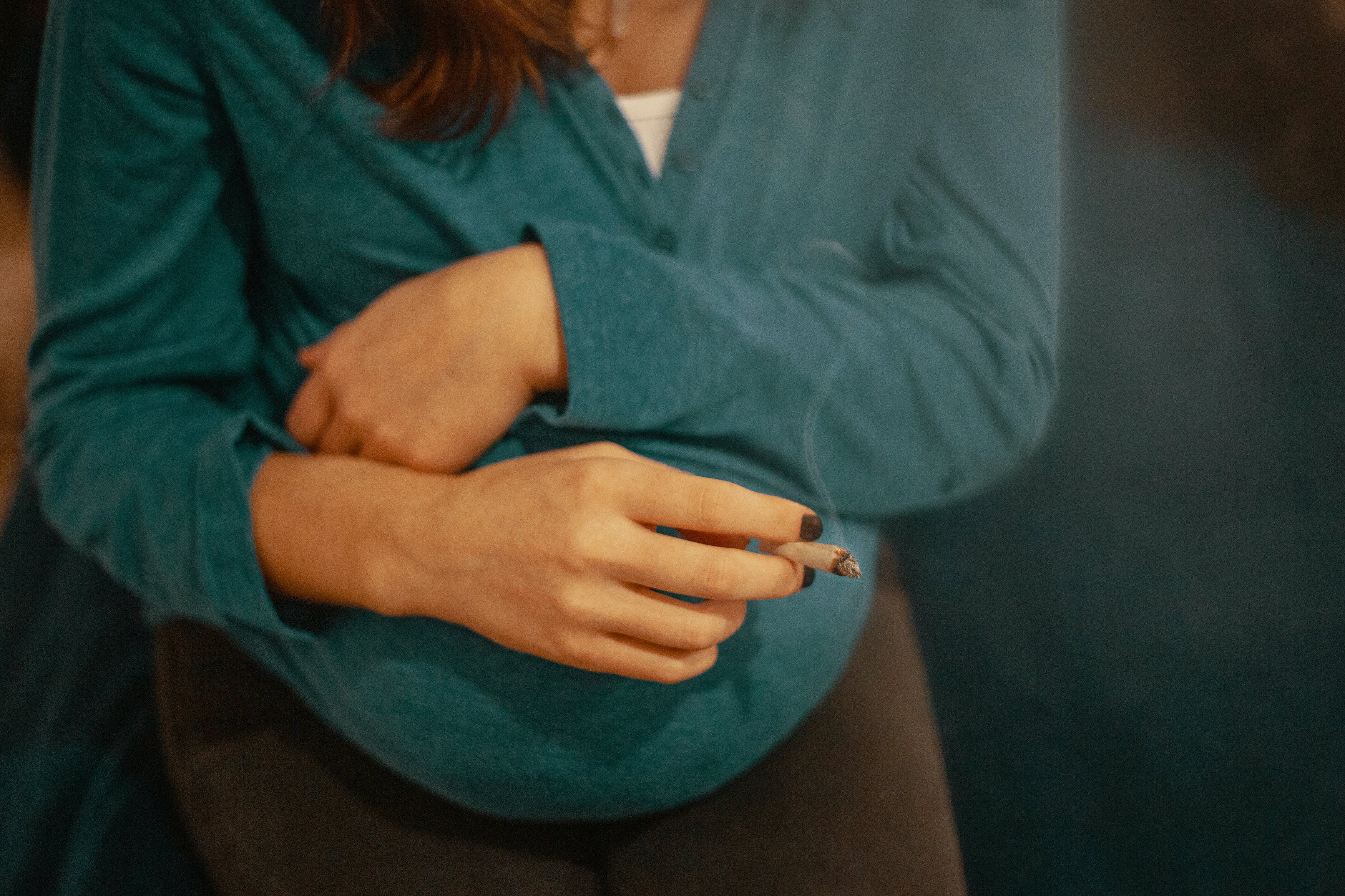 A woman holds a joint while crossing her hands over her pregnant stomach. Here's what you need to know about smoking weed during pregnancy