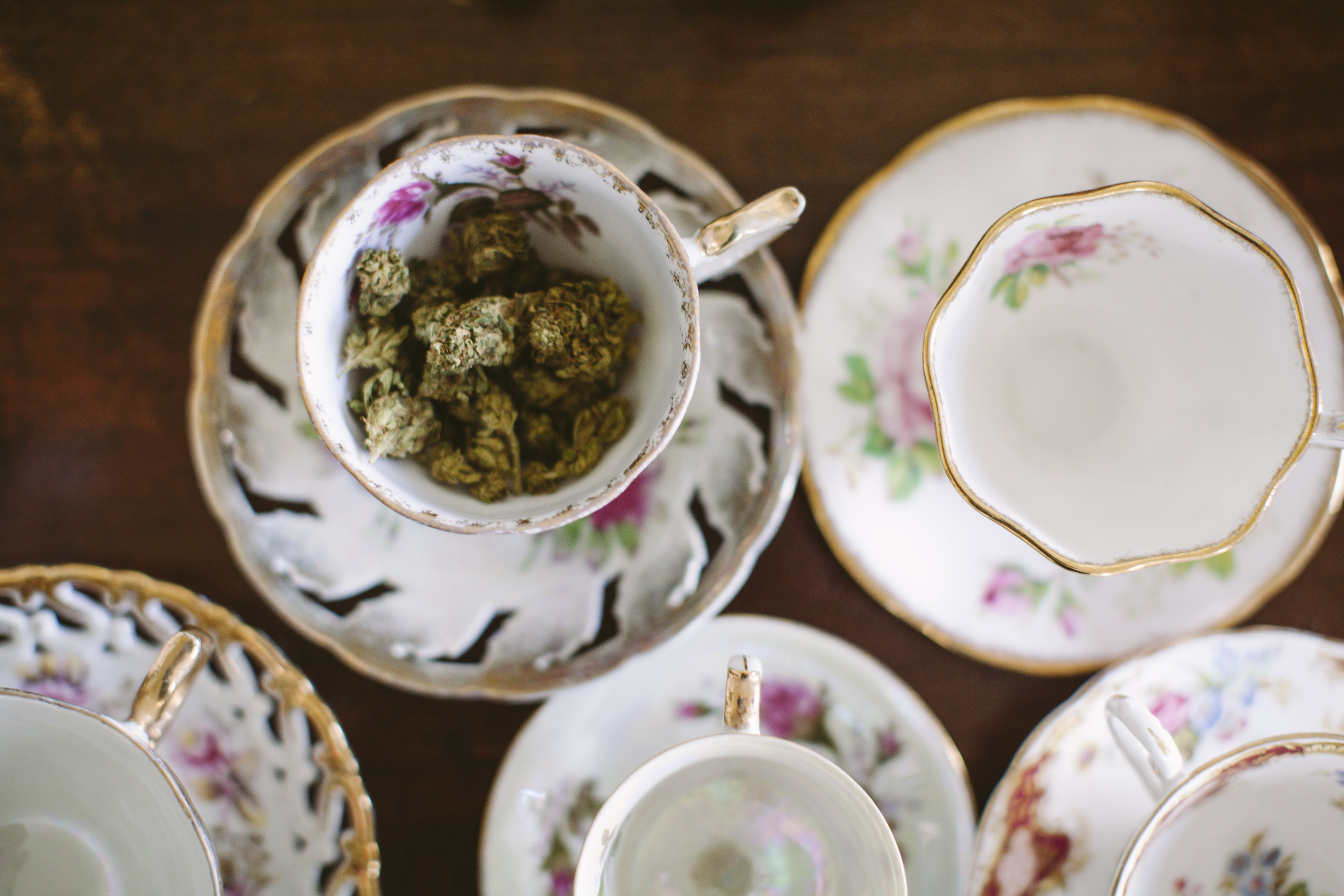 Cannabis sits inside a tea cup as someone prepares to make weed tea.