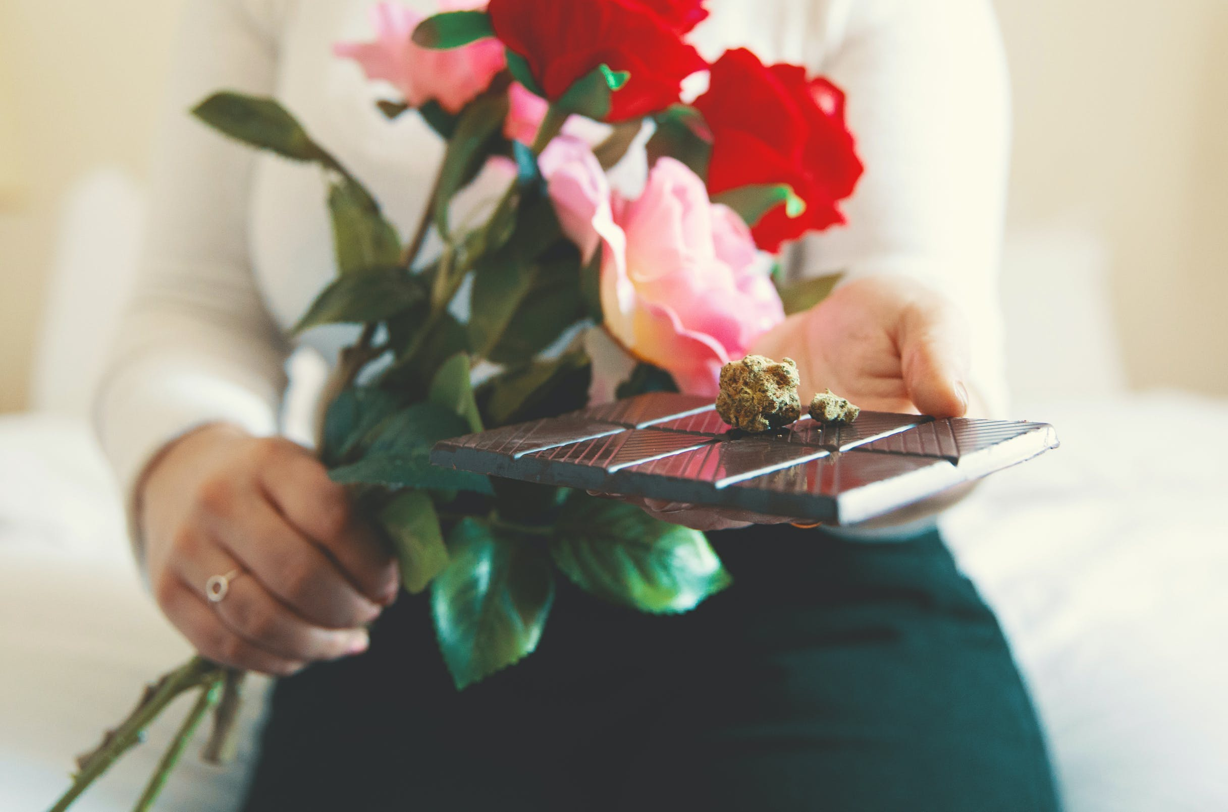 How to make weed chocolate: A woman holds a bouquet of roses with some dark chocolate and a nug of weed